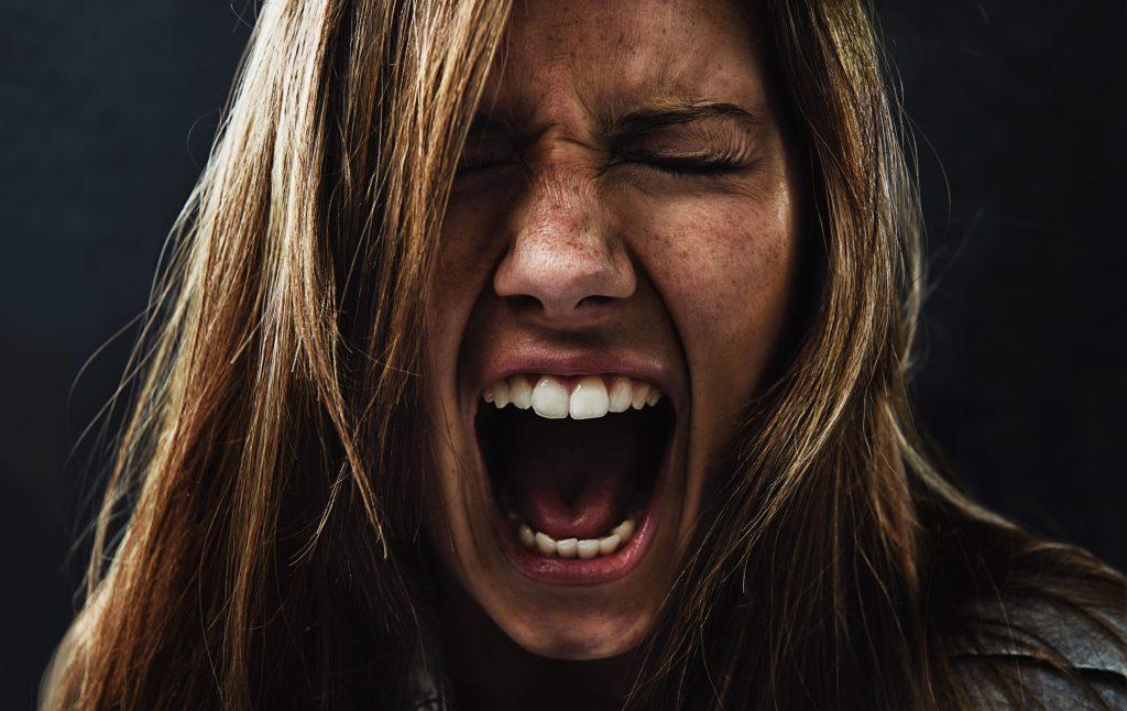 Auf diesem Bild siehst du eine Frau die ihrer Wut Ausdruck verleiht.